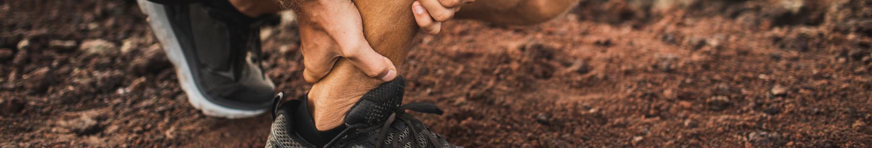 Zapalenie ścięgna Achillesa - biegacz trzymający się za bolące ścięgno.