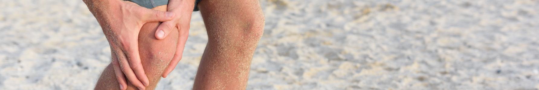 Objawy kolana skoczka - mężczyzna grający w siatkówkę plażową trzymający się za bolące kolano.