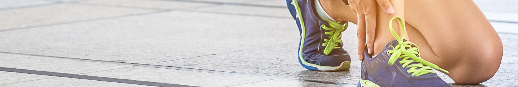 Objawy skręcenia kostki - kobieta po treningu trzymająca się za bolącą kostkę.