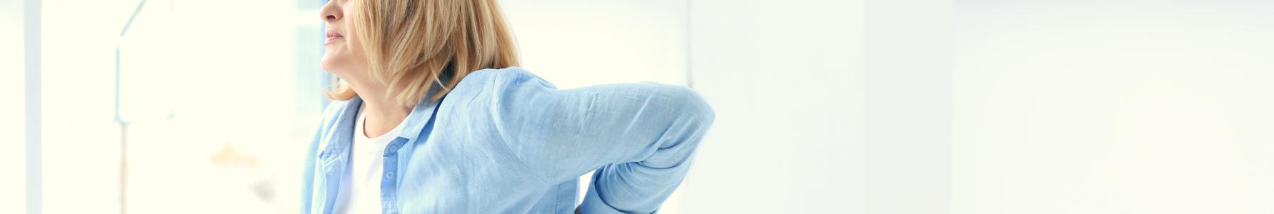 ZZSK - wstająca z kanapy kobieta trzymająca się za bolący kręgosłup.