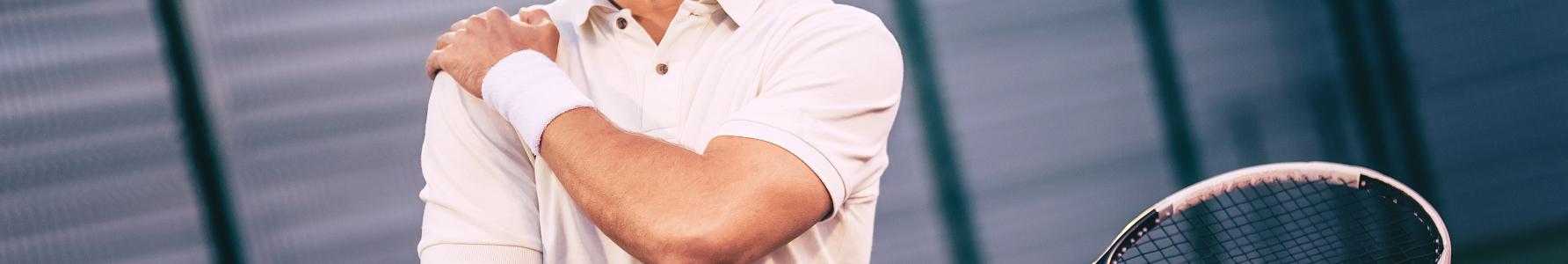 Uszkodzony stożek rotatorów - tenisista trzymający się za bolący bark.