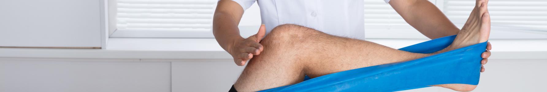 Jak wzmocnić kolana - mężczyzna wykonujący ćwiczenia na kolana pod kontrolą fizjoterapeuty.