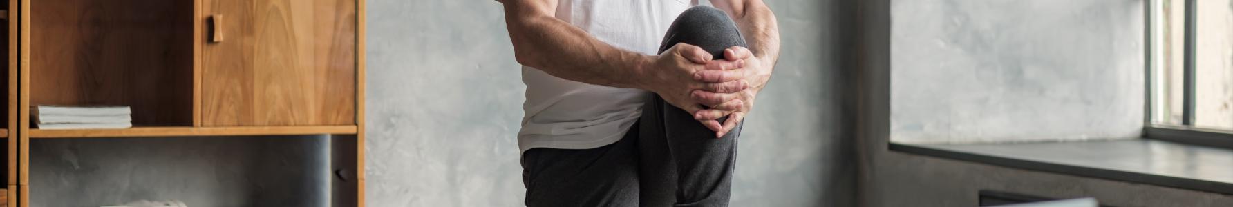 Rozgrzewka przed treningiem - starszy mężczyzna wykonujący w domu ćwiczenia na rozgrzewkę.