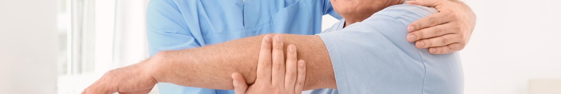 Metoda Feldenkraisa – fizjoterapeuta podczas ćwiczeń ze starszym mężczyzną.