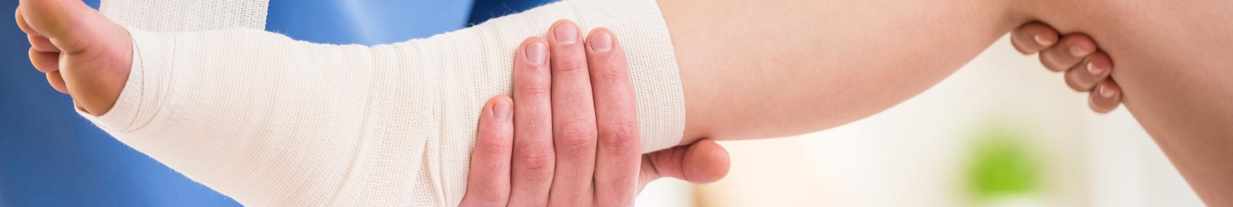 Stawy Charcota - lekarz bandażujący stopę pacjenta.
