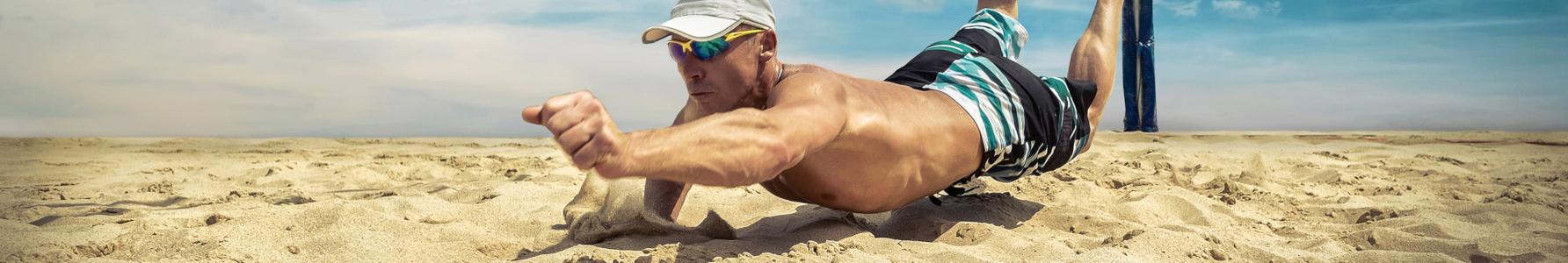 Mężczyzna grający w siatkówkę plażową próbujący podbić piłkę.